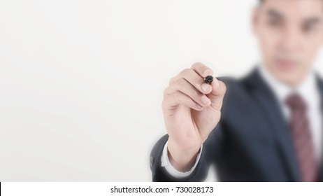 Businessman holding black color marker, writing on blank space for your text, design, wording. Selective focus on hand with blur background.