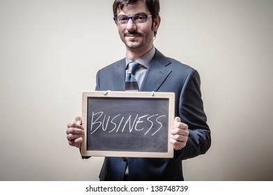 businessman holding blackboard written business on gray background