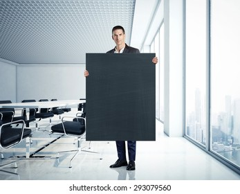 Businessman holding blank blackboard at contemporary office