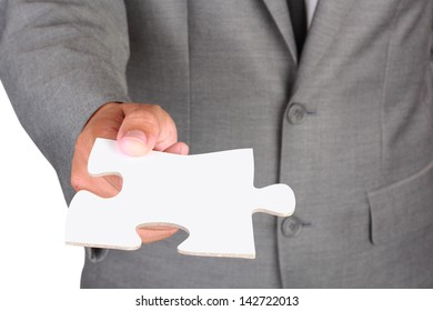 Businessman holding blank jigsaw isolated on white background with clipping path
