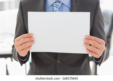 Businessman holding blank page in the office