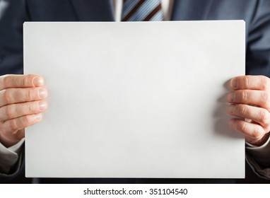 Businessman holding blank paper, copy space