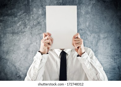 Businessman holding blank paper in front of his face with copy space for business message