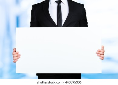 Businessman holding blank picture frame