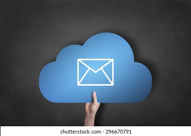 Businessman is holding a blue cloud mail icon on black blackboard
