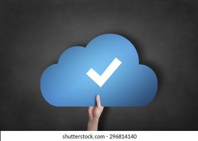 Businessman is holding a blue cloud tick icon on blackboard