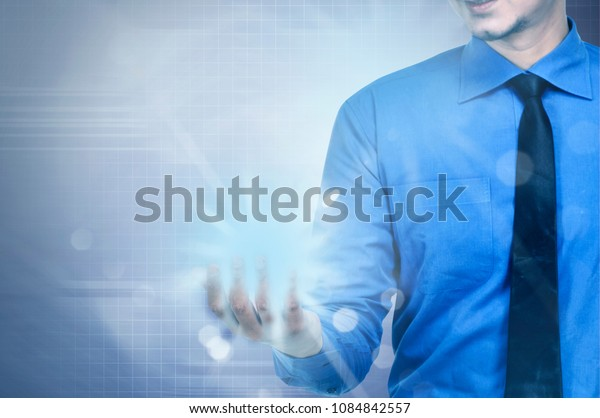 Businessman holding blue hologram with digital background