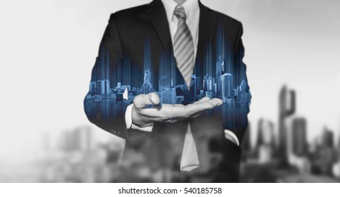 Businessman holding blue modern buildings hologram on hand, with black and white city background