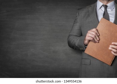Businessman holding a book in front of him