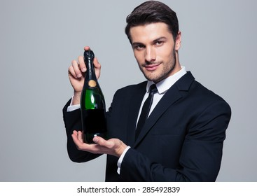 Businessman holding bottle of champagne over gray background. Looking at camera