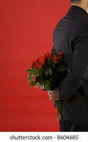 Businessman holding bouquet of roses behind his back. We don't see his face. Side view