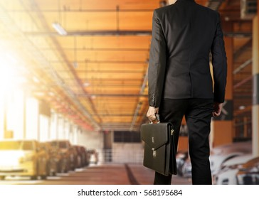 Businessman holding a briefcase in a parking lot on modern office
