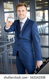 Businessman holding briefcase and showing a credit card in office