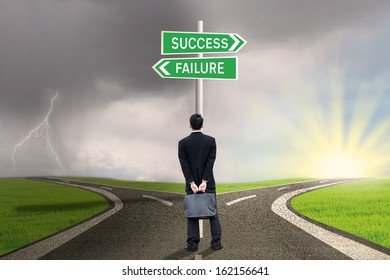 Businessman is holding briefcase and standing on the road with a sign of success or failure