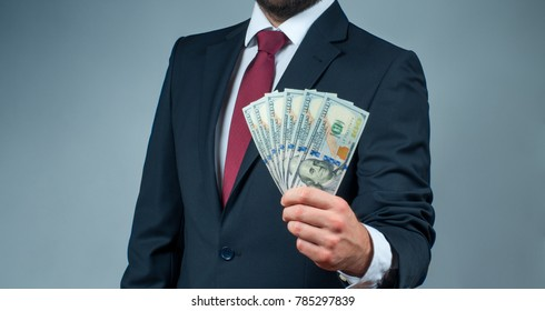 Businessman holding bunch of money banknotes. Finance, saving, salary and donate concept.