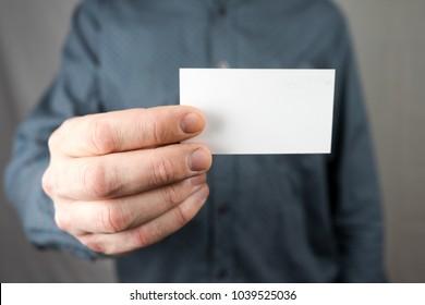Businessman holding a business card. Mock up.