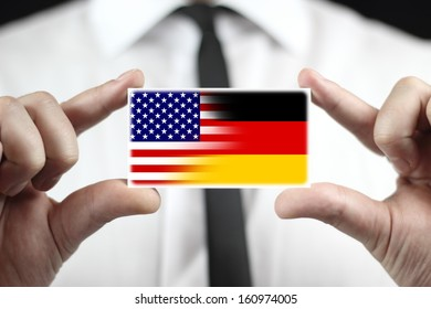 Businessman holding a business card with USA and Germany Flag
