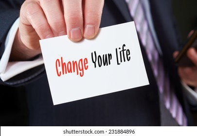 A businessman holding a business card with the words,  Change Your Life, written on it.