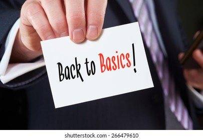 A businessman holding a business card with the words, Back to Basics, written on it.