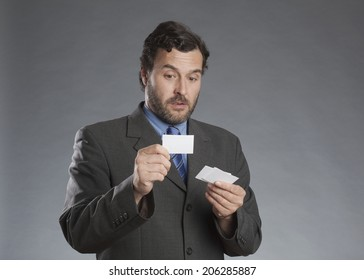 Businessman holding business cards against gray background