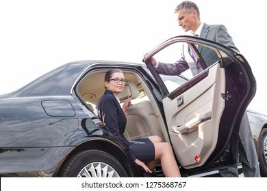 Businessman holding car door for colleague against sky