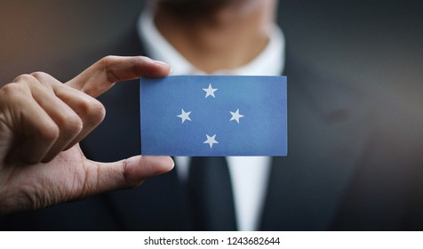 Businessman Holding Card of Federated States of Micronesia Flag