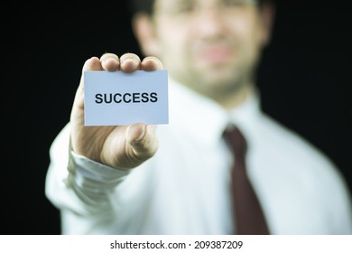 Businessman holding a card with success word