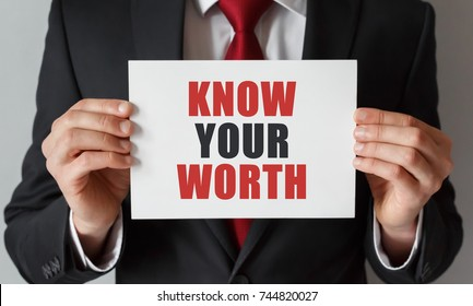 Businessman holding a card with text Know Your Worth