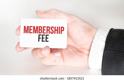 businessman holding a card with text MEMBERSHIP FEE