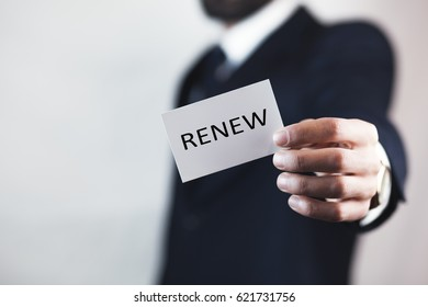 businessman holding a card with text renew
