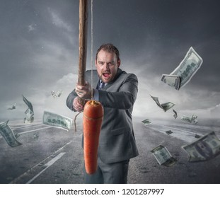 Businessman holding a carrot in a stick