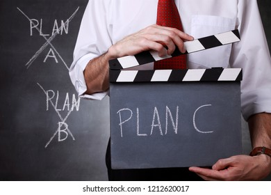 Businessman holding a clapper and ready to start with plan C