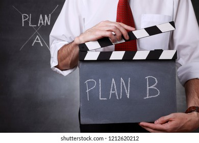Businessman holding a clapper and ready to start with plan B
