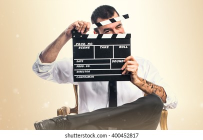 Businessman holding a clapperboard