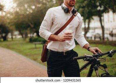 Businessman holding a coffee cup and walking to office taking his bicycle along. Man enjoying coffee while walking to work along with his bike.