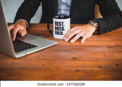 A businessman holding a coffee mug in his office with best boss ever written on the mug. Working on his wooden desk with a laptop