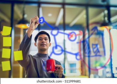 businessman holding coffee mug and writing data on transparent board