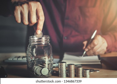 businessman holding coins putting in glass. concept saving money and finance accounting