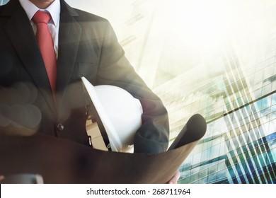 Businessman holding construction helmet and blueprints