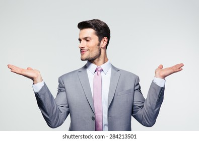 Businessman holding copyspace on the palms over gray background