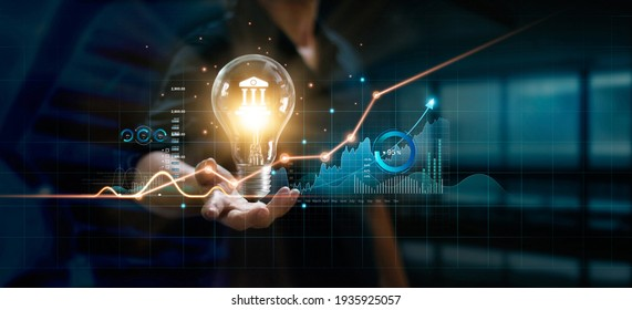 Businessman holding creative light bulb with growth graph and banking icons. Financial innovation technology develop new products and services that enhance successful and profit in global business. - Shutterstock ID 1935925057