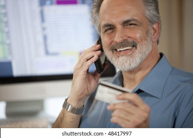 A businessman holding up a credit card and making a payment on his cellphone with a computer monitor in the background. Horizontal shot.