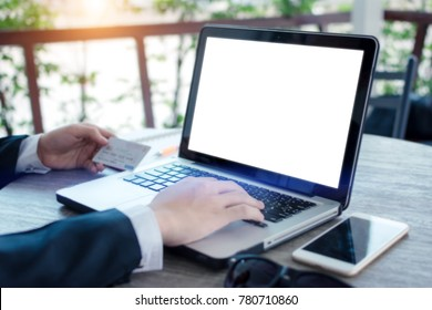 Businessman holding credit card and and typing text on white screen notebook at coffee shop.Online payment via internet.Online shopping.Trading via social media.For mockup