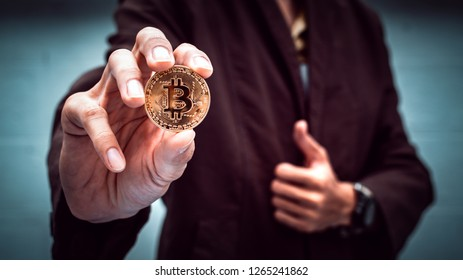 Businessman holding cryptocurrency bitcoin. Digital money for banking and international network payment with blockchain.