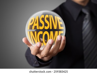 Businessman holding crystal ball with passive income concept
