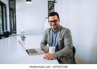 Businessman holding cup of coffee in office.