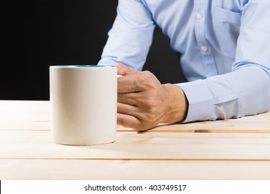 Businessman Holding a cup of coffee on wooden table