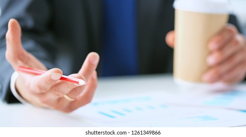 Businessman holding cup of coffee to take away and making notes with a red pen on the business graph on desk office.