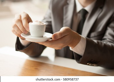 Businessman holding a Cup of coffee.This photo has a free space for your text.