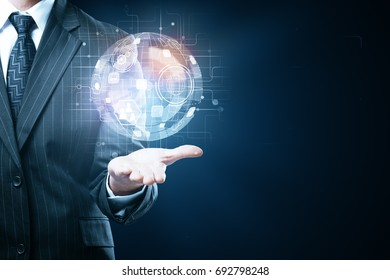 Businessman holding digital globe with business icons on blue background. Technology and innovatgion concept